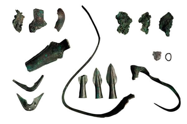 Resten van drie zwaarden, fragmenten van schedebeslagen en drie bronzen lanspunten uit een collectief elitegraf.